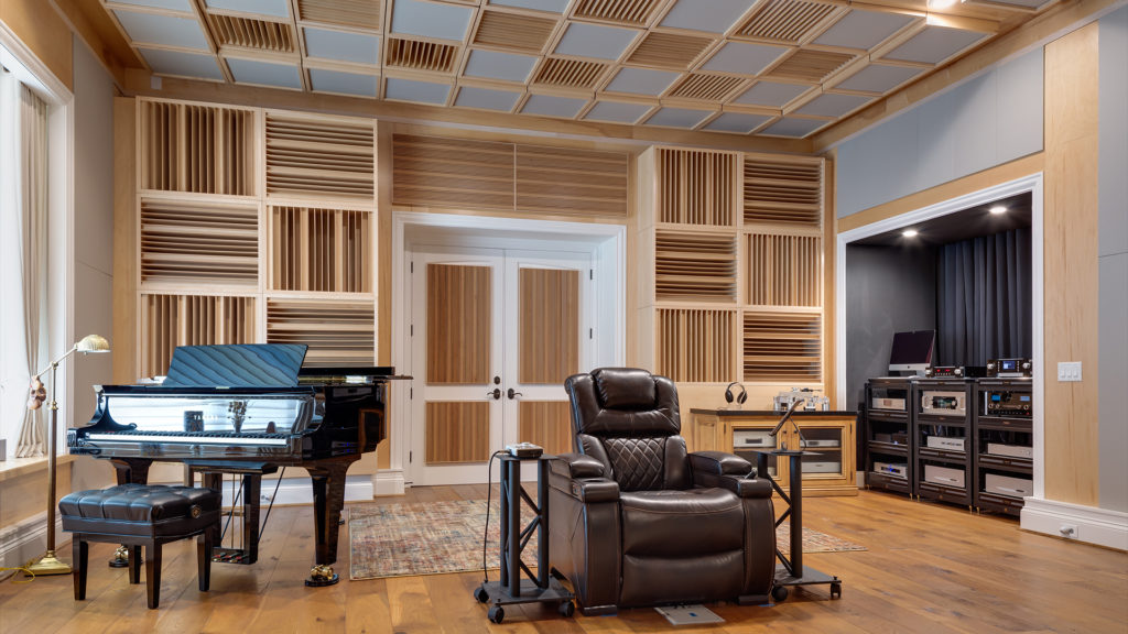 acoustically treated listening room with seat, piano and sound diffusers on the walls